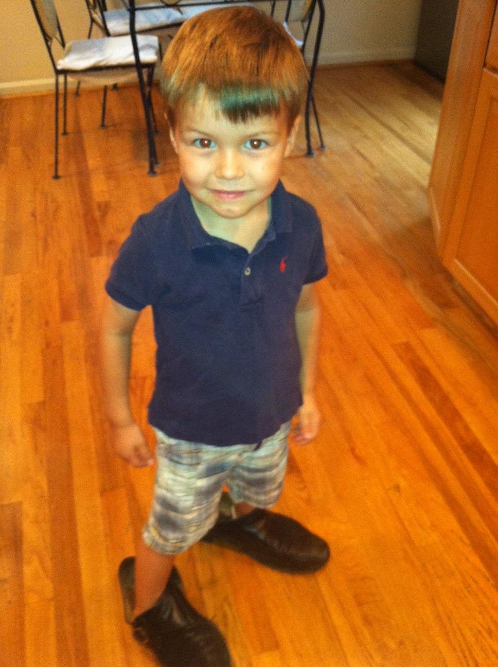 little boy wearing big shoes